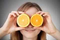 Muchacha rubia hermosa que usa la naranja como vidrios fotografía de archivo libre de regalías