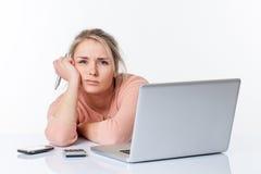 Muchacha rubia infeliz agotada que se inclina en su escritorio escaso blanco Imagenes de archivo