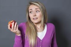 Muchacha rubia inocente que resiste en la consumición de una manzana apetitosa Imágenes de archivo libres de regalías