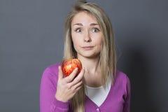 Muchacha rubia inocente que se pregunta alrededor por una manzana en su mano Imagenes de archivo