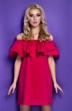 Muchacha rubia joven atractiva en vestido rojo fotografía de archivo