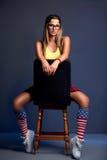 Muchacha rubia joven atractiva que se sienta en silla Imágenes de archivo libres de regalías