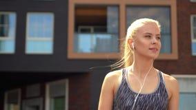 Muchacha rubia joven, atractiva y deportiva en ropa de deportes que escucha la música al aire libre Atención sanitaria y forma de
