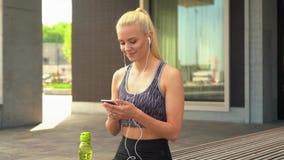 Muchacha rubia joven, atractiva y deportiva en ropa de deportes que escucha la música y la relajación al aire libre Atención sani