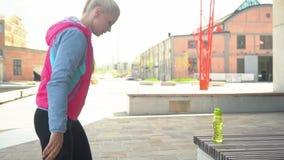 Muchacha rubia joven, atractiva y deportiva que hace los ejercicios del calentamiento al aire libre Atención sanitaria y forma de