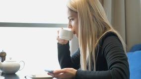 Muchacha rubia joven bonita con el teléfono que se sienta en una tabla en un café almacen de video