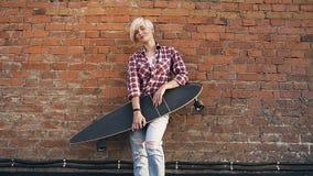 Muchacha rubia joven con el longboard que se coloca en el tejado cerca de la pared de ladrillo roja en la puesta del sol Muchacha almacen de metraje de vídeo