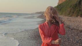 Muchacha rubia joven con el pelo largo en blusa roja encendido metrajes