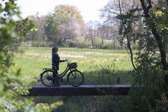 Muchacha rubia joven con la bicicleta entre follaje verde fresco de la primavera Foto de archivo libre de regalías
