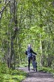 Muchacha rubia joven con la bicicleta entre follaje verde fresco de la primavera Imagen de archivo libre de regalías