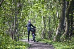 Muchacha rubia joven con la bicicleta entre follaje verde fresco de la primavera Fotografía de archivo libre de regalías