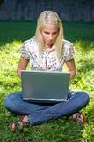 Muchacha rubia joven con la computadora portátil al aire libre Foto de archivo libre de regalías