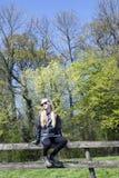 Muchacha rubia joven con las gafas de sol en el SP fresco del verde del befrore de la cerca Imagen de archivo libre de regalías