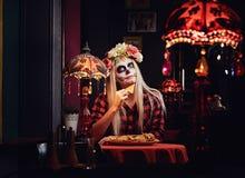 Muchacha rubia joven con maquillaje de los undead en guirnalda de la flor que come los nachos en un restaurante mexicano imágenes de archivo libres de regalías