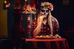 Muchacha rubia joven con maquillaje de los undead en guirnalda de la flor que come los nachos en un restaurante mexicano imagenes de archivo