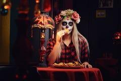Muchacha rubia joven con maquillaje de los undead en guirnalda de la flor que come los nachos en un restaurante mexicano foto de archivo libre de regalías