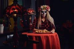 Muchacha rubia joven con maquillaje de los undead en guirnalda de la flor que come los nachos en un restaurante mexicano fotos de archivo