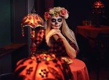 Muchacha rubia joven con maquillaje de los undead en guirnalda de la flor que come los nachos en un restaurante mexicano fotos de archivo libres de regalías