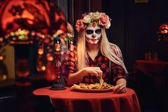 Muchacha rubia joven con maquillaje de los undead en guirnalda de la flor que come los nachos en un restaurante mexicano imagen de archivo