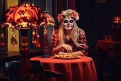 Muchacha rubia joven con maquillaje de los undead en guirnalda de la flor que come los nachos en un restaurante mexicano fotografía de archivo