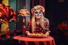 Muchacha rubia joven con maquillaje de los undead en guirnalda de la flor que come los nachos en un restaurante mexicano imagen de archivo libre de regalías