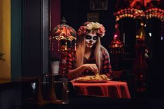 Muchacha rubia joven con maquillaje de los undead en guirnalda de la flor que come los nachos en un restaurante mexicano foto de archivo