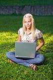 Muchacha rubia joven de Attarctive con la computadora portátil en naturaleza. Fotos de archivo