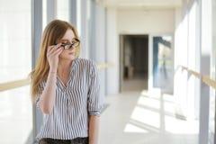 Muchacha rubia joven de la empresaria o del estudiante que mira la cámara Mujer en gafas de sol en universuty Educación, entrenan Fotos de archivo libres de regalías