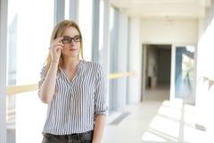 Muchacha rubia joven de la empresaria o del estudiante que mira la cámara Mujer en gafas de sol en universuty Educación, entrenan Foto de archivo libre de regalías