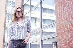 Muchacha rubia joven de la empresaria o del estudiante que mira la cámara Mujer en gafas de sol en universuty Educación, entrenan Foto de archivo