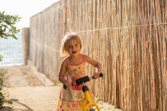Muchacha rubia joven del niño en el vestido que juega con la pequeña bici de la balanza Luz caliente de la puesta del sol Vacacio foto de archivo