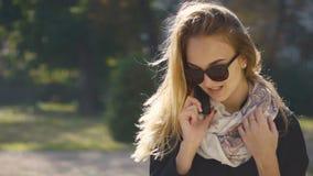 Muchacha rubia joven en gafas de sol que habla por el teléfono almacen de video