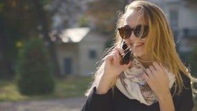 Muchacha rubia joven en gafas de sol que habla por el teléfono metrajes