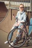 Muchacha rubia joven en las gafas de sol que se colocan con la bici del bmx y que usan smartphone en el skatepark Imagen de archivo