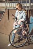 Muchacha rubia joven en las gafas de sol que se colocan con la bici del bmx y que usan smartphone en el skatepark Foto de archivo