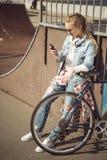 Muchacha rubia joven en las gafas de sol que se colocan con la bici del bmx y que usan smartphone en el skatepark Imagen de archivo libre de regalías