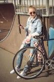 Muchacha rubia joven en las gafas de sol que se colocan con la bici del bmx y que usan smartphone en el skatepark Fotos de archivo