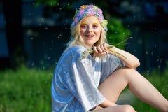 Muchacha rubia joven en sombrero chispeante con los dientes de león Imágenes de archivo libres de regalías