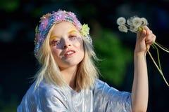 Muchacha rubia joven en sombrero chispeante con los dientes de león Imagen de archivo