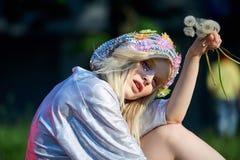 Muchacha rubia joven en sombrero chispeante con los dientes de león Fotos de archivo