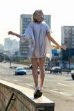 Muchacha rubia joven en sombrero chispeante que camina en la calle Fotografía de archivo