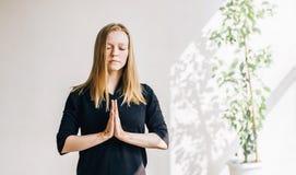 Muchacha rubia joven en un cuarto blanco que hace la meditación Fotos de archivo