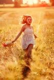 Muchacha rubia joven feliz en el vestido blanco con el funcionamiento del sombrero de paja Imágenes de archivo libres de regalías