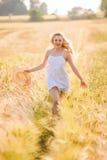 Muchacha rubia joven feliz en el vestido blanco con th corriente del sombrero de paja Imagen de archivo libre de regalías