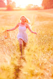 Muchacha rubia joven feliz en el vestido blanco con th corriente del sombrero de paja Foto de archivo