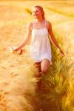 Muchacha rubia joven feliz en el vestido blanco con th corriente del sombrero de paja Imagen de archivo
