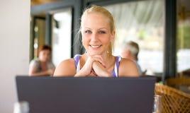 Muchacha rubia joven hermosa con su computadora portátil. Fotos de archivo libres de regalías