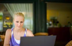 Muchacha rubia joven hermosa con su computadora portátil. Imagen de archivo