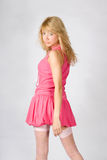 Muchacha rubia joven hermosa en color de rosa Imagenes de archivo