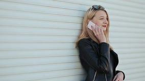 Muchacha rubia joven hermosa en la chaqueta de cuero y gafas de sol que habla en el teléfono móvil al aire libre Contra un fondo  metrajes